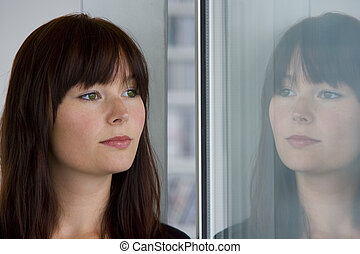 In Reflection - A beautiful young woman stares wistfully...