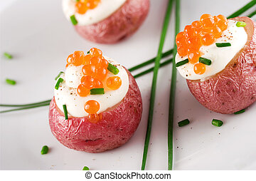 Potato with caviar - Roasted red potato topped with cream,...
