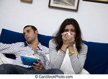 movie night - young couple watching a romantic movie on tv....