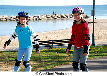 Girls rollerblade - Two girls rollerblading on lake shore...
