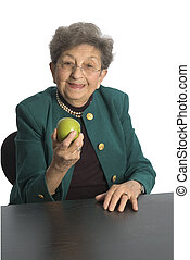 woman eating an apple - attractive senior citizen about to...