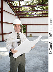 Construction Inspector with Blueprints - A construction...