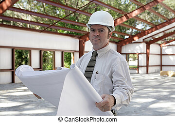 Engineer on Jobsite - A construction engineer reviewing...