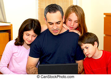 Family computer - Father and children looking into a...