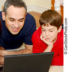 Father son computer - Father and son lying on the floor at...