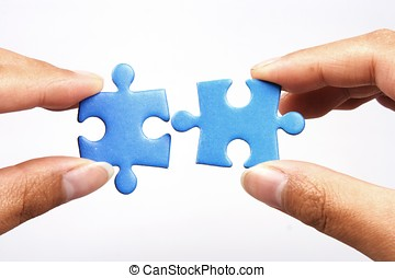 Holding Jigsaw Puzzle - Hands holding two jigsaw puzlle for...