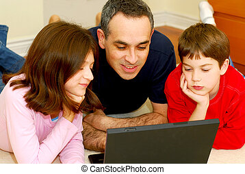 Family computer - Father and children lying on the floor at...