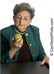 senior woman with apple - attractive senior woman about to...