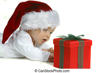 Baby Santa - A baby wearing a Santa hat looking at a gift