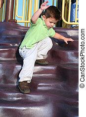Careful Descent - Young boy balancing as he carefully climbs...