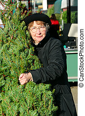 Senior woman at the Christmas tree market with her Christmas...