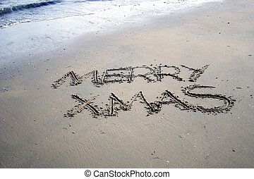 merry christmas written in the sand