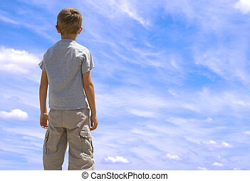 Boy Looking Toward Sky - Young boy looking up twoards blue...