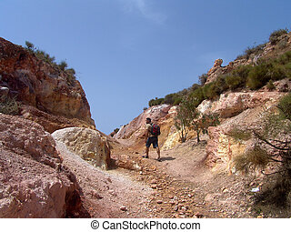 hiking at Vulcano island - man with backpack hiking in a...