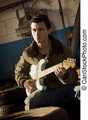 guitarist - cool guy playing blues in a garage