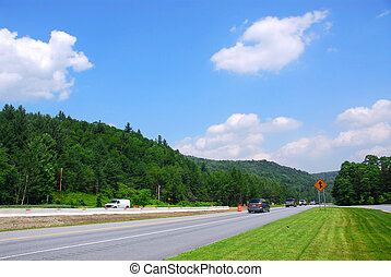 Highway - Divided highway among green hills on sunny summer...
