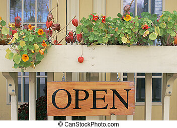 Open for business - Open sign with gorgeous flowers lining a...