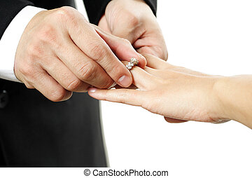 Wedding - The groom inserting a diamond ring into the...