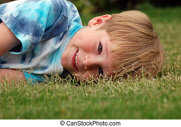 Boy Lying in Grass - A six year old boy lying down in the...
