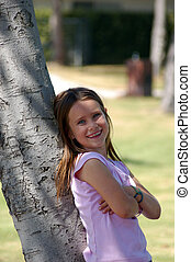 Girl Leaning on Tree - A pretty nine year old girl leaning...