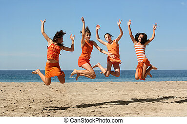 Four girls jumping - Four girls in orange clothes jumping on...