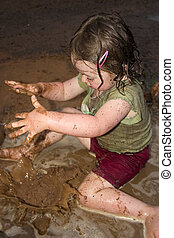 Splashing in the mud - a little girl dropping mud into a...
