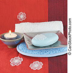 Burning candle and white flowers with soap in a dish