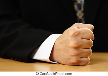 Businessman - A businessman with his firm fist on a table