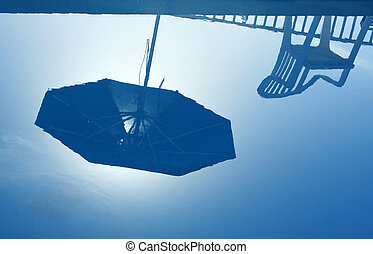 Summer Reflection - Reflection of parasol and chair in still...