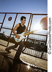 guitarist - cool guy playing his guitar against sunlight