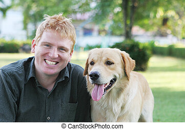 Mans best friend - Happy blond man in the park with his dog...