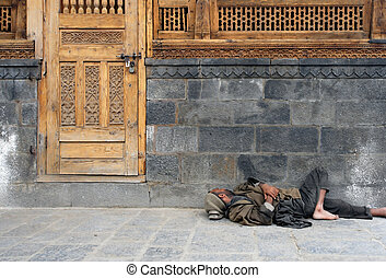 Poverty in India - Homeless man in India sleeping on the...