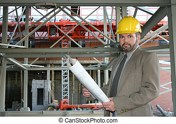 Boss - Man in suit at construction site holding bluerints...