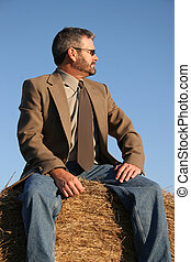 Haystack - Man in jacket, tie and jeans sitting on a...