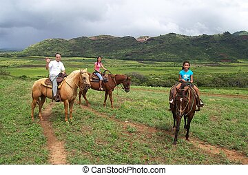 Family Rides Horses - Dad and daughters ride on horses.