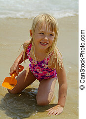 Girl at the beach - A smiling little girl playing in the...
