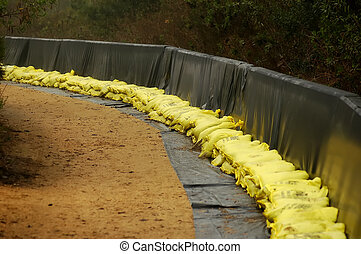 Sand Bags - Sand bags stacked against retaining wall ready...