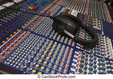 Mixing Desk and Headphones - Close up of an audio visual...