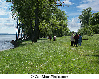 walking people - walking old people at the river Volga bank...