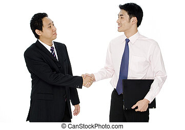 Business Deal - Two asian businessmen shake hands and...