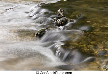 Rocks in a streamlet - Moss-covered rocks in a streamlet.