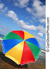 Rainbow Parasol - Rainbow parasol on the beach with dramatic...