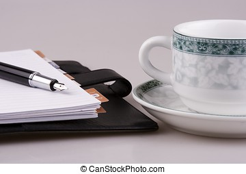 Cup and Organizer - A cup of coffee and organizer with...