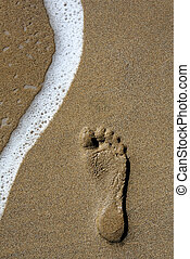 Footstep and Wave - Single footstep on golden sand beach...