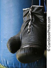Boxing Glove and Bag - Close up of black boxing glove...