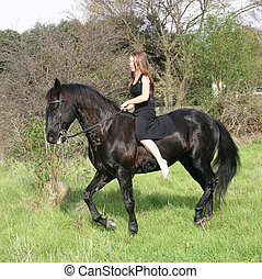 trotting girl - teenager and her black stallion in field
