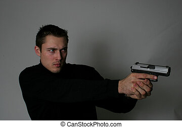 Man pointing gun - A man in a black shirt and in a dark...
