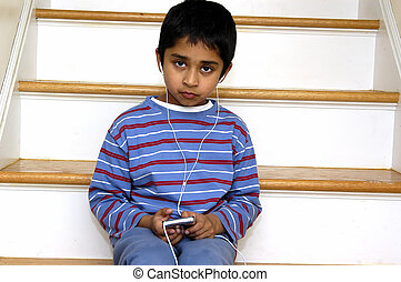 Kid listening to music - A cute kid listening to music using...