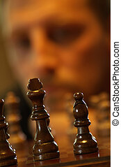Man Playing Chess - A man contemplating his next move in a...