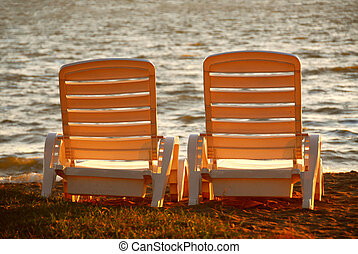 Beach chairs - Two plastic beach chairs on a shore in late...